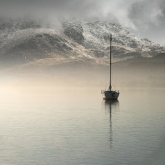 Stunning landscape image of sailing yacht sitting still in calm lake water with mountain looming in background during Autumn Fall sunrise - 255444189