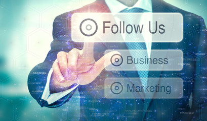 A business man selection a button on a futuristic display with a Follow Us concept written on it.
