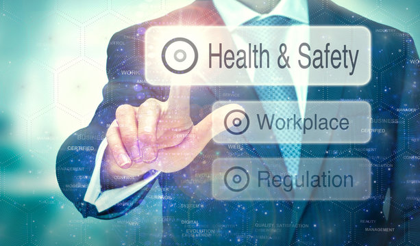 A business man selection a button on a futuristic display with a Health and Safety concept written on it.