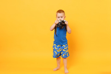 Kid boy 3-4 years old in blue beach summer clothes hold retro camera isolated on bright yellow orange wall background children studio portrait. People childhood lifestyle concept Mock up copy space.
