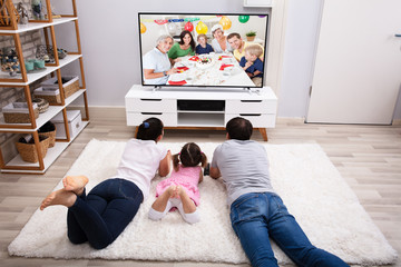 Family Watching Television At Home