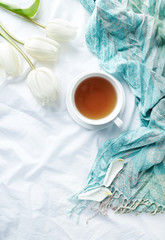Cup of morning tea and flowers in bed. Flat lay. Copy space