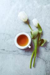 A cup of tea and white spring tulips on gray stone background. Flat lay. Copy space