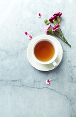 A cup of tea and dianthus flowers on gray stone background. Flat lay. Copy space