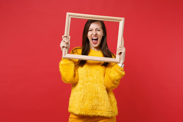 Portrait of crazy young woman in yellow fur sweater screaming, holding picture frame isolated on bright red wall background in studio. People sincere emotions, lifestyle concept. Mock up copy space.