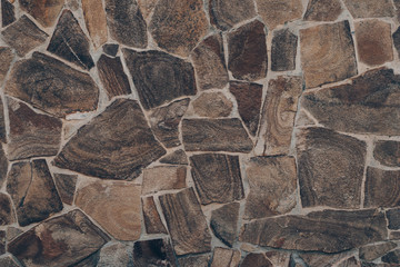 Dark brown stone wall texture. Abstract dark brown rock wall background. Construction exterior architecture.