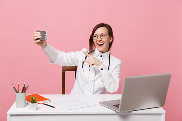 Female doctor sit at desk work on computer with medical document hold cellphone in hospital isolated on pastel pink background. Woman in medical gown glasses stethoscope. Healthcare medicine concept.