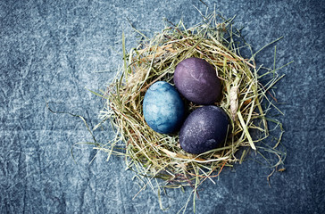 Natural colored Easter eggs in a hay nest. Flat lay. Copy space