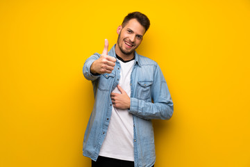 Handsome man over yellow wall with thumbs up because something good has happened