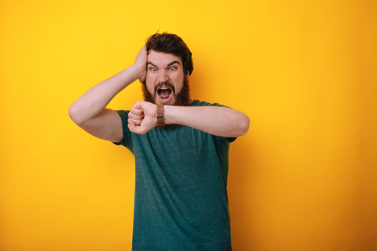 Image of astonished man looking at wrist watch touching his head being late posing isolated over yellow background