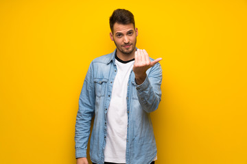 Handsome man over yellow wall inviting to come with hand. Happy that you came