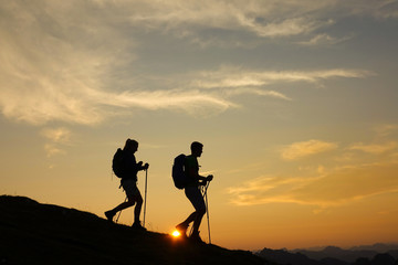 SILHOUETTE: Active tourists are hiking down a grassy hill in the peaceful Alps.