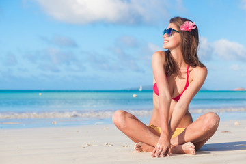 woman in swimsuit with hibiscus flower in her hair relaxing at tropical beach. Praslin, Seychelles