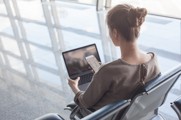 woman working with laptop in airport waiting her flight