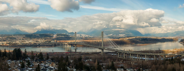 Panoramic view of Port Mann going across Fraser River during a sunny winter day. Taken in Surrey, Vancouver, British Columbia, Canada.