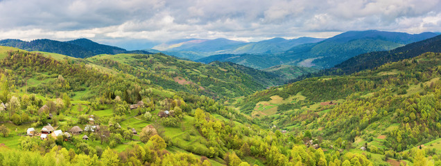 panorama of mountainous countryside in springtime. village on the hillside, mountain ridge in the distance. overcast weather. view from the hill.