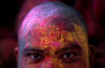 """Man daubed in colours looks on as he takes part in """"Lathmar Holi"""" celebrations inside a temple in the town of Barsana"""