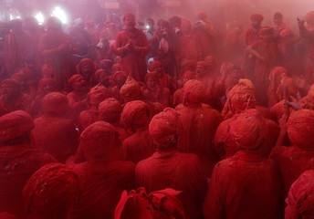 """Men daubed in colours sing religious hymns as they take part in """"Lathmar Holi"""" celebrations inside a temple in the town of Barsana"""