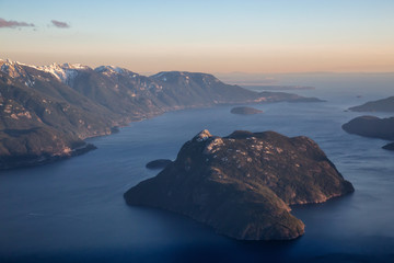 Aerial view of Canadian Mountain Landscape during a vibrant sunset. Taken in Howe Sound near Squamish, North of Vancouver, British Columbia, Canada.