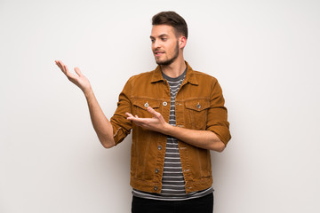 Handsome man over white wall extending hands to the side for inviting to come
