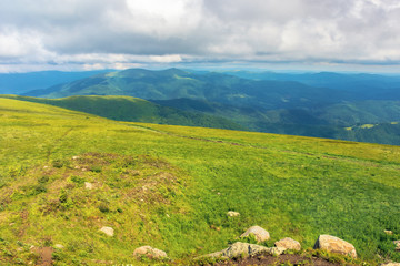 mountain landscape in summer with cloudy sky. green grassy meadow with some rocks on the hill. ridge in the distance. beautiful carpathian nature scenery on a sunny day