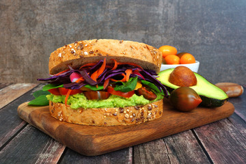 Superfood sandwich with avocado, tomatoes, and vegetables on whole grain bread. Side view on wood paddle board against a dark background.