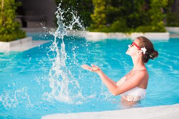 young beautiful woman in white bikini relaxing in luxury spa pool