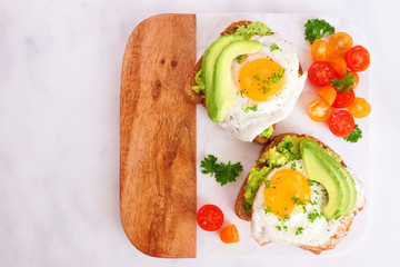 Avocado toasts with eggs and tomatoes on whole grain bread. Top view on a marble and wood platter.