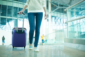 leg view of a woman in hurry with cabin size bag in airport