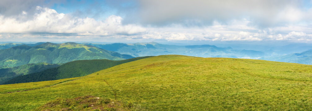 panorama of a mountain landscape in summer. beautiful scenery with low hanging clouds. huge grassy alpine meadow. dividing mountain ridge in the distance. location runa, ukraine