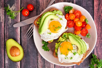 Avocado toasts with eggs and tomatoes on whole grain bread. Above view on a dark wood background.