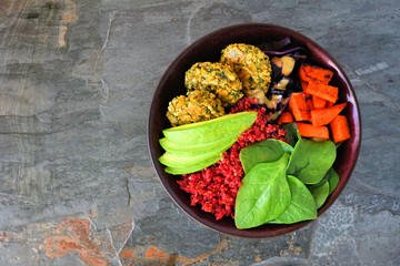 Healthy vegan buddha bowl with falafels, beet quinoa, avocado, and vegetables. Top view on a dark stone background. Healthy eating concept.