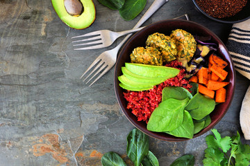 Healthy vegan buddha bowl with falafels, beet quinoa, avocado, and vegetables on a dark stone background. Healthy eating concept. Corner border with copy space.