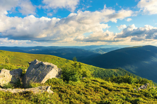 mountain landscape in summer with cloudy sky in evening. green grassy meadow with some rocks on the hill. ridge in the distance. beautiful carpathian nature scenery on a sunny afternoon