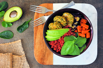 Healthy vegan lunch bowl with falafels, beet quinoa, avocado, and vegetables. Above view table scene. Healthy eating concept.