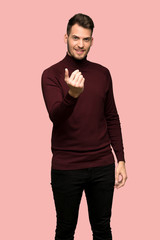 Man with turtleneck sweater inviting to come with hand. Happy that you came over pink background