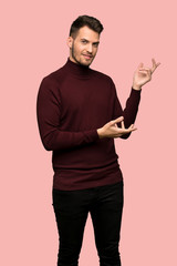 Man with turtleneck sweater extending hands to the side for inviting to come over pink background