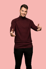 Man with turtleneck sweater presenting and inviting to come with hand over pink background