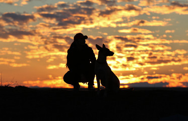 Silhouette of a girl and dogs against the backdrop of an incredible sunset, sky and clouds. Belgian Shepherd Malinois