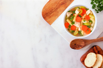Homemade chicken noodle soup with vegetables. Overhead view on a white marble background with copy space.
