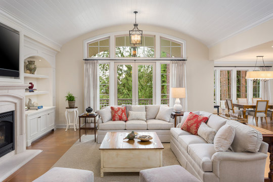 elegant living room in new luxury home with hardwood floors, fireplace, french doors, and furniture