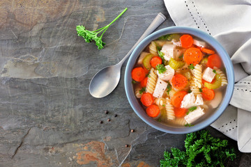 Homemade chicken noodle soup with vegetables. Above scene on a dark slate background.