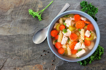 Homemade chicken noodle soup with vegetables. Overhead view on a dark slate background.
