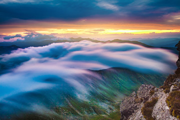 Long exposure clouds moving over mountain ridge at sunset landscape