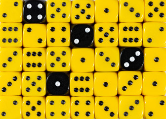 Background of random ordered yellow dices with four black cubes