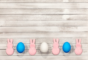 White wooden easter background with pink bunnies, white and blue easter eggs