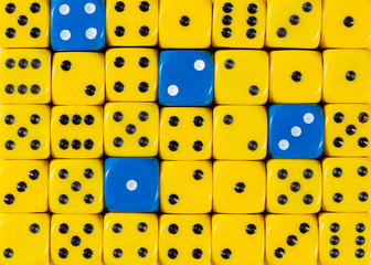 Background of random ordered yellow dices with four blue cubes