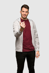 Man with sweatshirt inviting to come with hand. Happy that you came over grey background