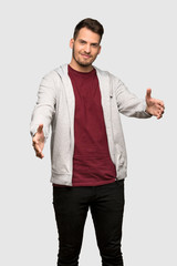 Man with sweatshirt presenting and inviting to come with hand over grey background