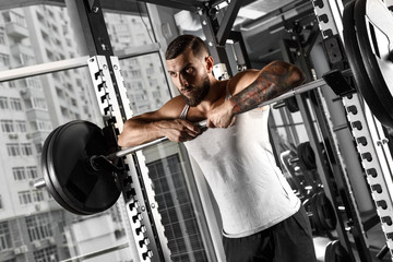 Bodybuilding. Bearded man standing leaning on barbell at gym looking forward sassy